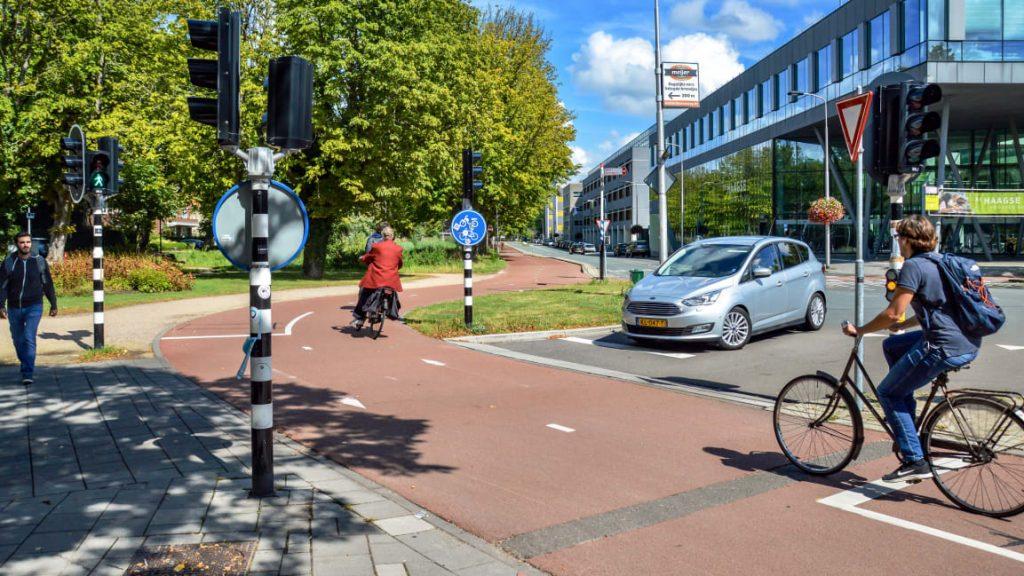 Ak chcú autá na križovatke prejsť cez svetelnú križovatku, musia počkať kým prejdú cyklisti